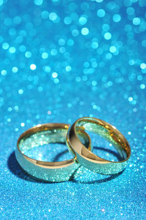 cordiality: Two golden rings on turquoise glitter background Stock Photo