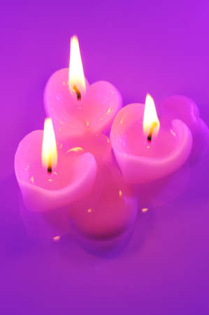 mothersday: three melting candle pink hearts in purple light