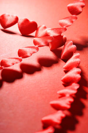 cordiality: chain of small red textile arts before on red background
