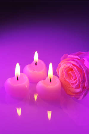 cordiality: three luminous pink candle hearts with pink rose in purple light Stock Photo