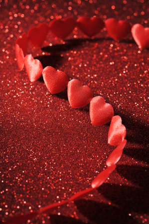 cordiality: chain of textile arts before on red sparkle background Stock Photo