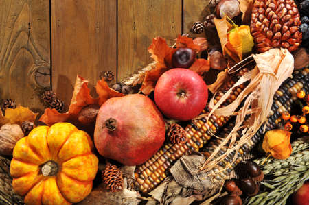 mealie: pumpkin, pomegranate, apple, nuts, berries and grain on old weathered wooden floor Stock Photo