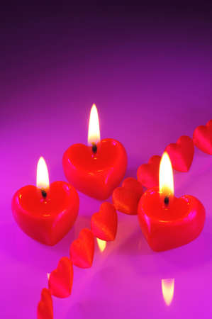 cordiality: Three luminous red candle with hearts textile arts before Stock Photo