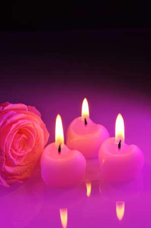 agradecimiento: Tres corazones velas rosadas luminosas con rosa rosa en luz púrpura