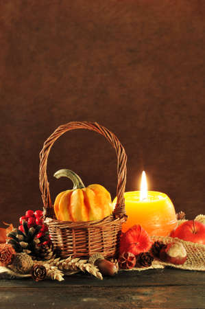 cucurbit: Small pumpkin in basket on old weathered wooden floor in candlelight Stock Photo