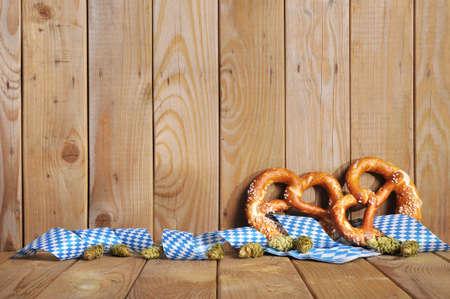 Zwei original bayerischen Salzbrezeln weich und Hopfen mit bayerischen Rautenmuster vor verwitterten Holzbrett Standard-Bild