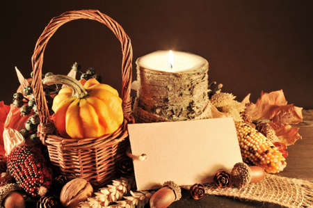 Small pumpkin in basket on old weathered wooden floor in candlelight with copyspace Banco de Imagens