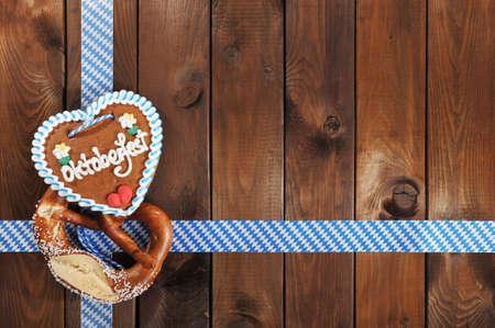 Original Bavarian salted pretzel soft and Oktoberfest gingerbread heart from Germany in front of wooden board Banco de Imagens