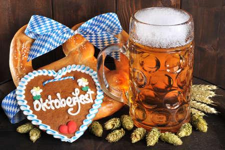 Original Bavarian Oktoberfest big soft pretzel with beer mug and hops gingerbread heart from Germany on old beer barrel