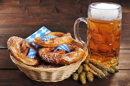 Original Bavarian Oktoberfest pretzels salted soft in a basket with beer from Germany on wooden board Banco de Imagens