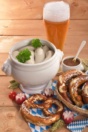 veal sausage: Bavarian veal sausage breakfast with sausages, soft pretzel, wheat beer and mild mustard on wooden board