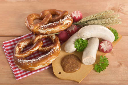 veal sausage: Bavarian veal sausage breakfast with sausages soft, pretzel and mild mustard on wooden board Stock Photo