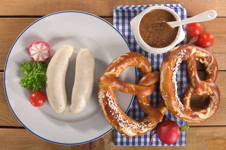 veal sausage: Bavarian veal sausage breakfast with two sausages, soft pretzels and mustard mild on wooden board