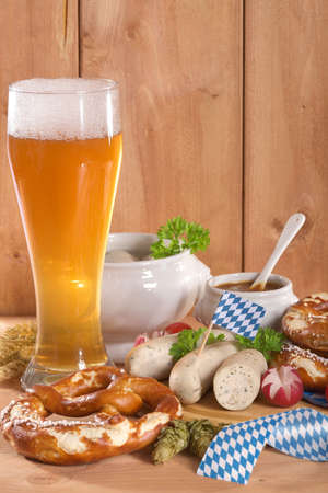 beerglass: Bavarian veal sausage breakfast with sausages, soft pretzel, wheat beer and mild mustard on wooden board