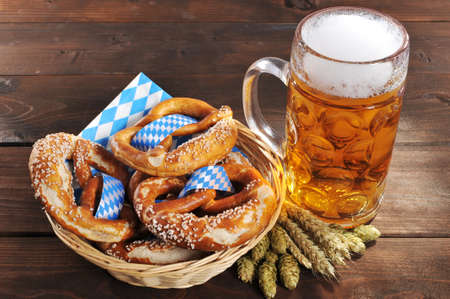 Original Bavarian Oktoberfest pretzels salted soft in a basket with beer from Germany on wooden board Foto de archivo