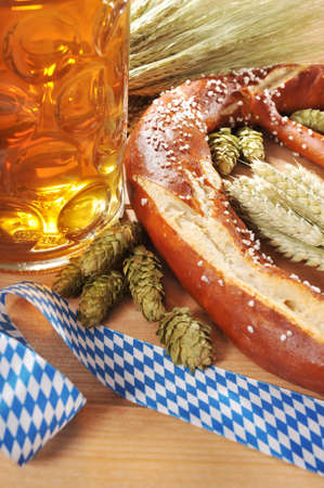 beerglass: original German Bavarian Oktoberfest pretzel with beer mug big soft hops, and wheat on old weathered wooden board