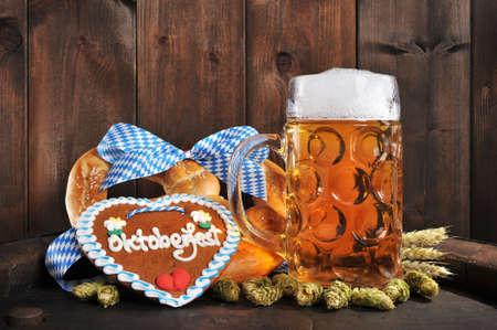 gingerbread heart: Original Bavarian Oktoberfest big soft pretzel with beer mug hops, and gingerbread heart from Germany on old beer barrel