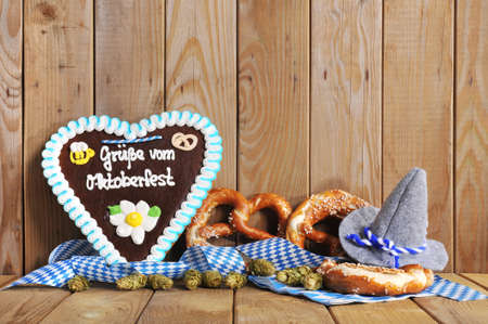 gingerbread heart: Regards from the Oktoberfest - original bavarian gingerbread heart with Oktoberfesthat and soft pretzels from Germany in front of OLT wooden board