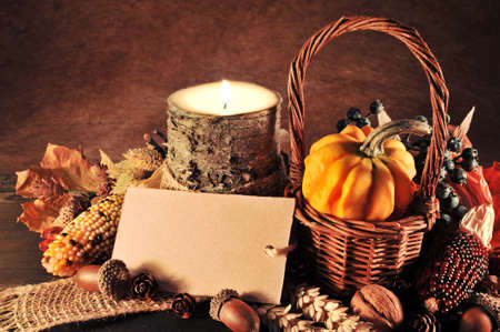 wooden basket: Small pumpkin in basket on old weathered wooden floor in candlelight with copyspace Stock Photo