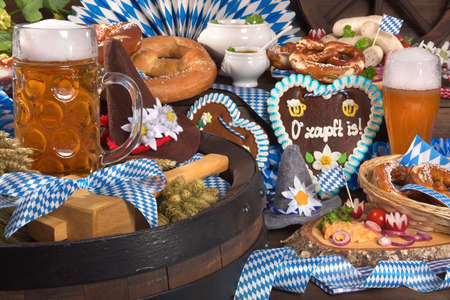 All typical German Bavarian symbols in one picture. Gingerbread heart with The beer is tapped text, soft pretzels, Bavarian veal sausage and beer. Banco de Imagens