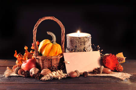 fall harvest: Small pumpkin in basket on old weathered wooden floor in candlelight with copyspace Stock Photo