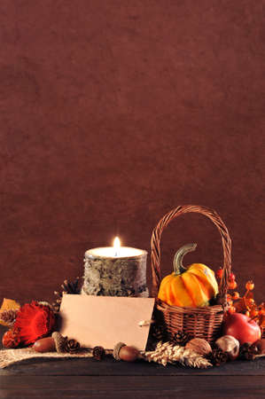 harvest time: Small pumpkin in basket on old weathered wooden floor in candlelight with copyspace Stock Photo