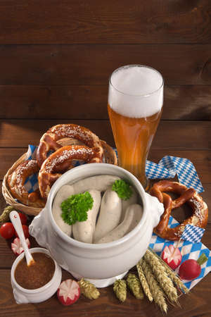 beerglass: Bavarian veal sausage breakfast with sausages, wheat beer, soft pretzel and mild mustard on dark weathered wooden board from Germany