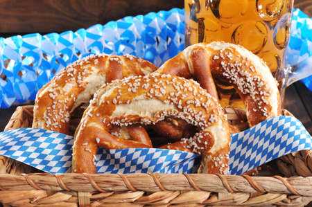 beerglass: Three original Bavarian salted pretzels with beer soft from Germany in front of wooden board