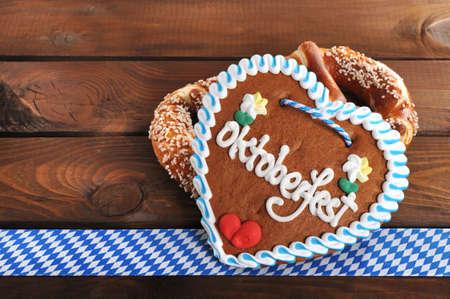 gingerbread heart: Original Bavarian salted pretzels soft Oktoberfest gingerbread heart from Germany in front of wooden board Stock Photo