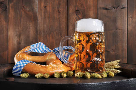 Original Bavarian Oktoberfest big soft pretzel with beer mug hops, and wheat from Germany on old beer barrel
