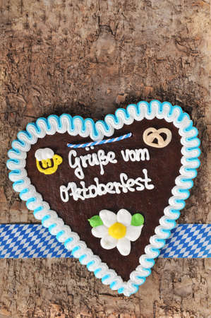 gingerbread heart: Regards from the Oktoberfest - original Bavarian Oktoberfest gingerbread heart from Germany on real brown tree bark Stock Photo
