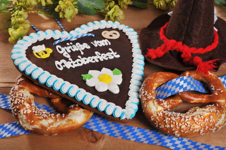 gingerbread heart: Regards from the Oktoberfest - original bavarian gingerbread heart with Oktoberfesthat and soft pretzels from Germany Stock Photo