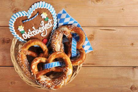 Original Bayerisches Oktoberfest Brezeln auf Holzbrett weich mit Lebkuchenherz in einem Korb aus Deutschland gesalzen