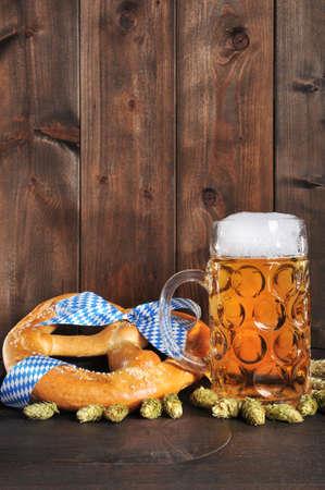 Original Bavarian Oktoberfest big soft pretzel with beer mug hops, and wheat from Germany on old beer barrel