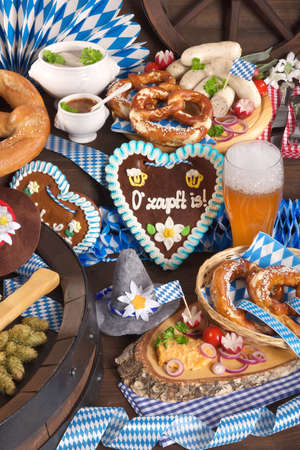 beerglass: All typical German Bavarian symbols in one picture. Gingerbread heart with The beer is tapped text, soft pretzels, Bavarian veal sausage and beer. Stock Photo