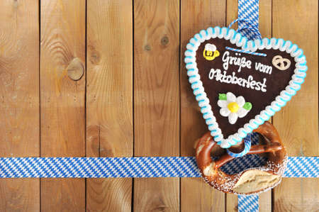 gingerbread heart: Regards from the Oktoberfest - original Bavarian salted pretzel soft and Oktoberfest gingerbread heart from Germany in front of wooden board