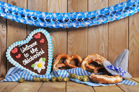 gingerbread heart: Welcome to the Oktoberfest - original bavarian gingerbread heart with Oktoberfesthat and soft pretzels from Germany in front of OLT wooden board
