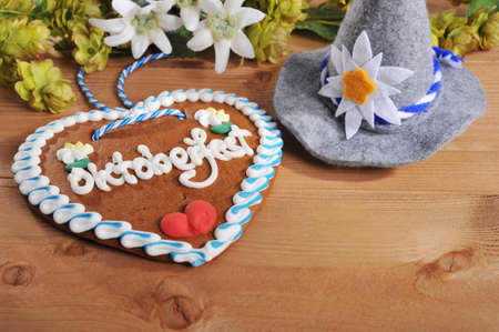 gingerbread heart: Regards from the Oktoberfest - original bavarian gingerbread heart with Oktoberfesthat and hops on wooden board from Germany