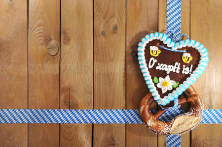 gingerbread heart: The beer is tapped - original Bavarian salted pretzel soft and Oktoberfest gingerbread heart from Germany in front of wooden board Stock Photo