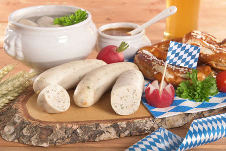 veal sausage: Bavarian veal sausage breakfast with sausages, wheat beer, soft pretzel and mild mustard on dark weathered wooden board