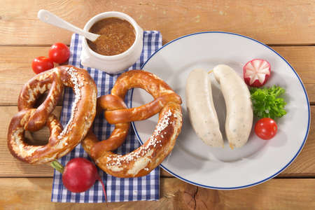 veal sausage: Bavarian veal sausage breakfast with two sausages, soft pretzels and mustard mild on wooden board from Germany