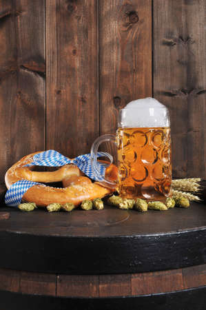 Original Bavarian Oktoberfest big soft pretzel with beer mug hops, and wheat from Germany on old beer barrel 版權商用圖片 - 44171759