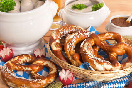 veal sausage: Bavarian veal sausage breakfast with sausages soft, pretzel, wheat beer and mild mustard on wooden board from Germany
