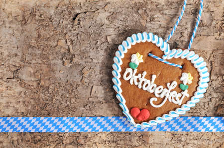 oktoberfest: Original Bavarian Oktoberfest gingerbread heart from Germany on real brown tree bark Stock Photo