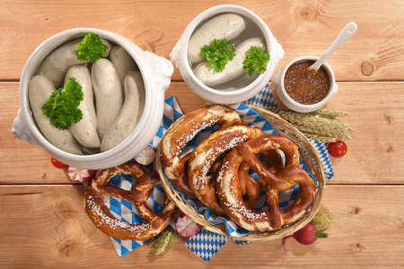 beerglass: Bavarian veal sausage breakfast with sausages soft, pretzel, wheat beer and mild mustard on wooden board from Germany