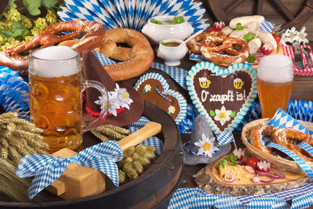 gingerbread heart: All typical German Bavarian symbols in one picture. Gingerbread heart with The beer is tapped text, soft pretzels, Bavarian veal sausage and beer. Stock Photo