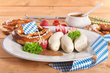 veal sausage: Bavarian veal sausage breakfast with sausages soft, pretzel and mild mustard on dark weathered wooden board from Germany Stock Photo