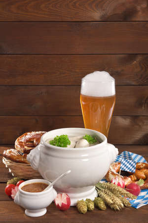 veal sausage: Bavarian veal sausage breakfast with sausages, wheat beer, soft pretzel and mild mustard on dark weathered wooden board from Germany