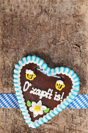 The beer is tapped - original Bavarian Oktoberfest gingerbread heart from Germany on real brown tree bark