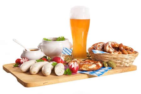 Weißwurst-Frühstück mit Würstchen weich, Brezel, Weißbier und einem milden Senf auf Holzbrett aus Deutschland